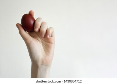 Unrecognizable women hand holding up an egg. Knocking a red Easter egg. Old holiday tradition. Isolated on white background. Text empty space. Happy Easter!