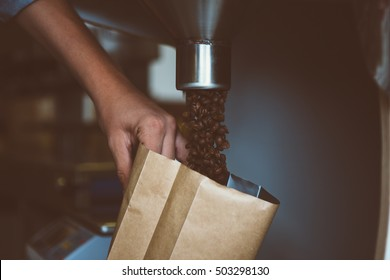 Unrecognizable worker holding bag and filling it with coffee beans