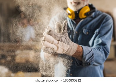 Unrecognizable worker is rubbing his work gloves to clean them from sawdust