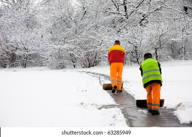 Unrecognizable workers removing first snow from pavement in park
