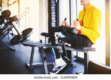 Unrecognizable young athlete with a prosthetic leg working out on a calf machine. Side view. Horizontal.