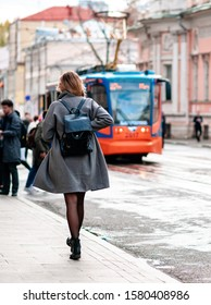 Unrecognizable young blond woman in a short light coat rush to tramway. Black stylish backpack on her back. Female in black stockings walking along the street to the tram stop. Warm sunny autumn day