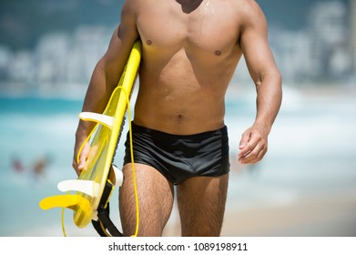 Unrecognizable young Brazilian surfer walking in a sunga with his surfboard along the shore at Arpoador beach, the popular surf break in Rio de Janeiro, Brazil