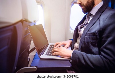 Unrecognizable young businessman with notebook sitting inside an airplane