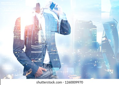 Unrecognizable young businessman talking on smartphone standing over Moscow city background. Toned image double exposure