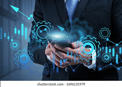 Unrecognizable young businessman working with smartphone in blurry office with double exposure of blurry growing financial graph. Concept of stock market, success and investment. Toned image