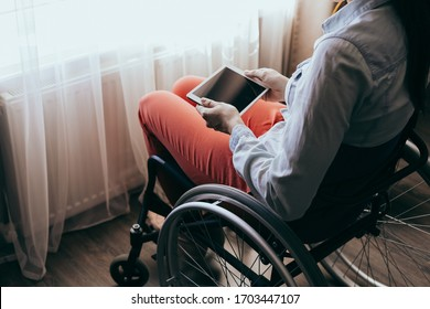 unrecognizable young disabled woman in a wheelchair with a modern tablet. Recovery and healthcare concepts.