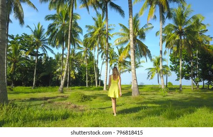 Unrecognizable young girl in yellow sundress on fun walk in palm tree plantation. Caucasian female enjoying a barefoot walk in a beautiful grassy park full of tall palm trees. Calming tropical scenery