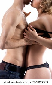 Unrecognizable young half naked couple love play, guy in jeans undressing girl, taking off her black bra, studio shot, white background, close-up