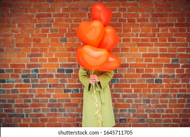unrecognizable young lady in green coat hold red air balloons in hands, she closed face with them. red brickwall in the background. celebration, birthday concept