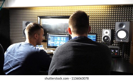 Unrecognizable young male audio editor and music producer working in the recording studio. Sound engineer creation a new song on personal computer. Rear back view Close up Slow motion.