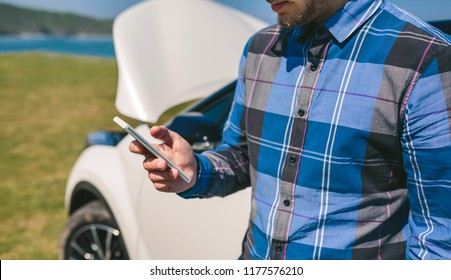 Unrecognizable young man with broken down car calling by mobile phone