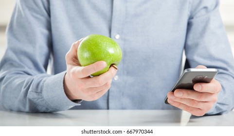 Unrecognizable young man eating fresh green apple and using his smartphone