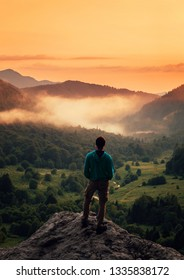 Unrecognizable young man standing on peak of cliff in summer mountains at sunset and enjoying view of nature, rear view.