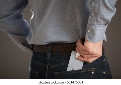Unrecognizable young man taking credit card out of his jeans pocket
