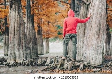 Unrecognizable young man wearing in hoody and cargo pants walking in autumn park.