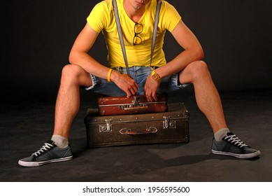 An unrecognizable young man in a yellow shirt and jean shorts sits on two old suitcases lying flat on the ground. No face.  Waiting. Isolated against a black background. Studio light. Night.
