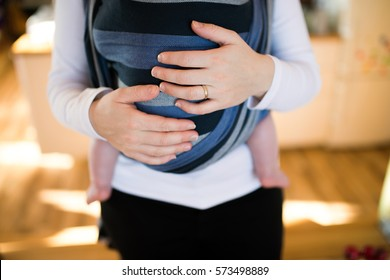 Unrecognizable young mother with her son in sling