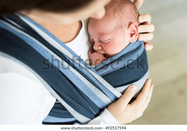 Madre joven irreconocible con su hijo en cabalgatas