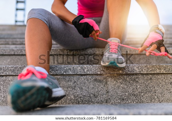 Unrecognizable young runner tying her shoelaces