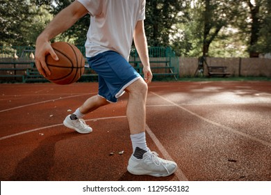 Unrecognizable young street basketball player showing his skills on court.