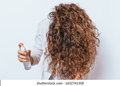 Unrecognizable young woman applying moisturizing spray to her beautiful curly hair, holding her head down.