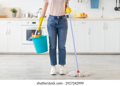 Unrecognizable young woman with bucket of cleaning supplies and mop ready to start wiping kitchen floor, indoors. Professional housekeeper doing domestic duties, cropped view
