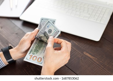 Unrecognizable young woman counting US Dollar on office table