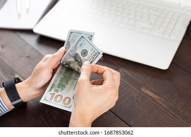 Unerkennbare junge Frau, die US-Dollar auf dem Präsidententisch zählt