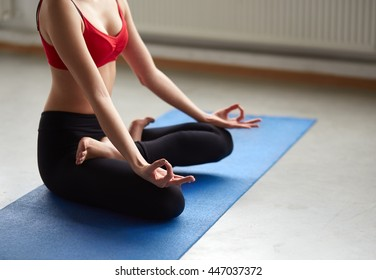 Unrecognizable young woman does yoga on mat indoors. Cropped portrait of girl sitting in seated cross legged pose relaxing in zen.