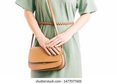 Unrecognizable young woman in green dress standing with brown handbag. Casual style, female beauty and fashion. Studio shot.