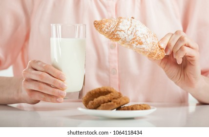 Unrecognizable young woman having croissant, oat cookies and milk for breakfast