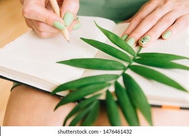 Unrecognizable young woman with notebook, a pen and green palm leaf. Girl writing romantic notes.