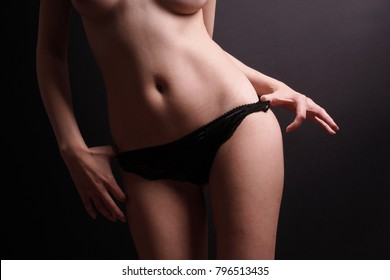 unrecognizable young woman pulling down panties. striptease or seduction concept. body part on black background.