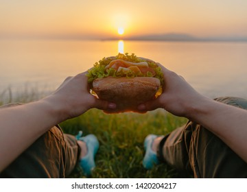 Unrecognizable young woman relaxing on coast by the sea with fast food fresh tasty burger and enjoying view of summer sunset, point of view.