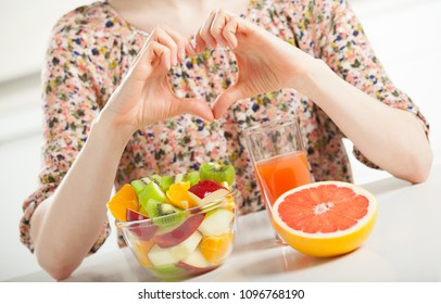 Unrecognizable young woman showing heart sign in front of the table with fresh fruit breakast illustrating her position towards healthy lifestyle