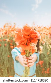Unrecognizable young woman standing in flower field and giving a bouquet of red poppies in summer, focus on flowers.