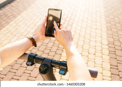 Unrecognizable young woman using smartphone while standing with electric scooter in street outdoor, point of view in first person.
