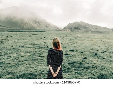 Unrecognizable young woman wearing in dress walking in summer mountains, rear view.