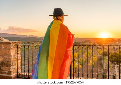 Unrecognizable young woman wrapped in rainbow gay flag at sunset in countryside.LGBT pride flag concept lifestyle.