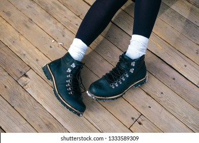 Unrecognizable young woman's feet in white high socks and black boots. Girl walking in the city.