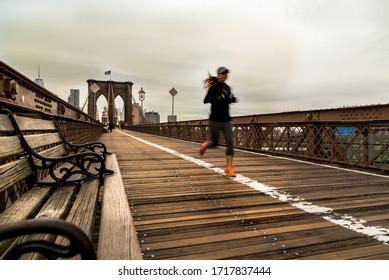 Unrecognizeable girl running on Brooklyn Bridge