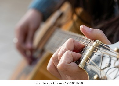 Unrecognized concentrated woman playing guitar outdoors. Selective focus.