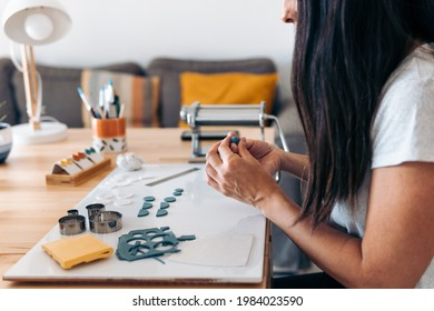 Unrecognized craftswoman sitting at home and making handmade jewelry with clay.