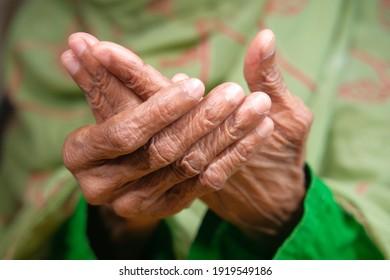unrecognized elderly women hands suffering wrist pain,