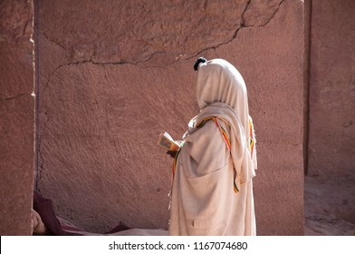 Unrecognized figure covered in white clothes standing with Bible in hand near orthodox church in Lalibela and praying