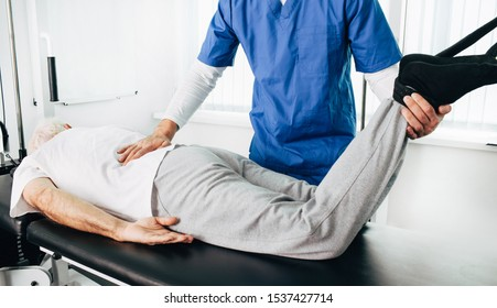 unrecognized kinesiologist doing therapeutic exercises for an elderly patient. Kinesitherapy at the medical center
