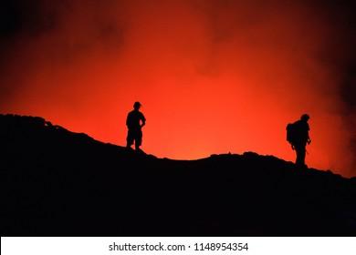 Unrecognized Tourists's silhouettes on Erta Ale Volcano edge illuminated with lava. Danakil Depression, Ethiopia, East Africa