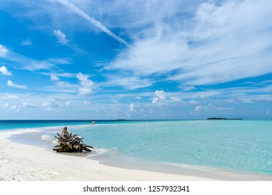 An unrecognized woman sitting on the tree truck on the sandbank with the two unrecognised women and islands in background in Maldives