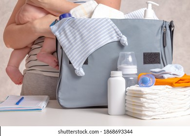 Unrecognizible caucasian woman packing big blue diaper bag for a walk or small trip with infant baby. Diapers, nappy, hat, bottle and other necessary things for journey with baby.